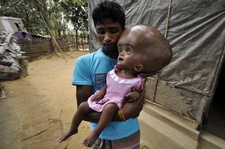 Indiano de 18 anos segura sua filha de um ano e seis meses no coloAridam Day/AFP